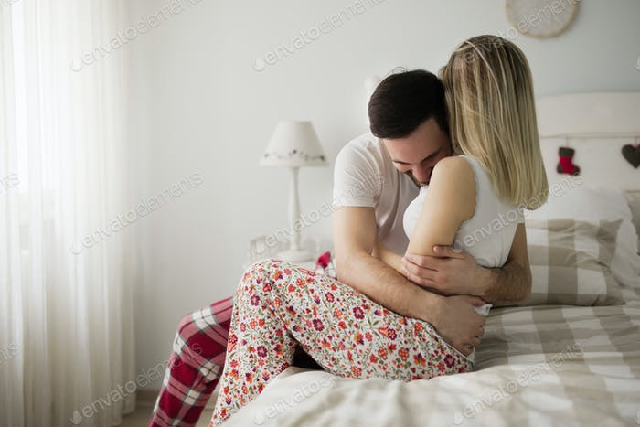 Picture of young attractive couple hugging on bed