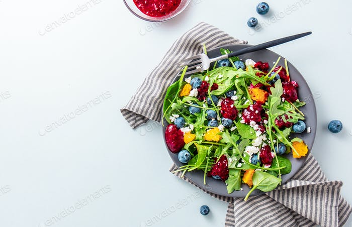 Summer salad with salad leaves, fruits, berries and cheese