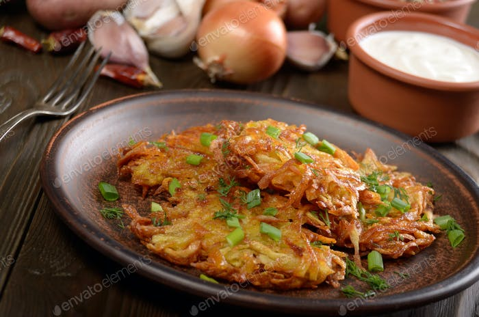 Fresh homemade tasty potato pancakes in clay dish with vegetable
