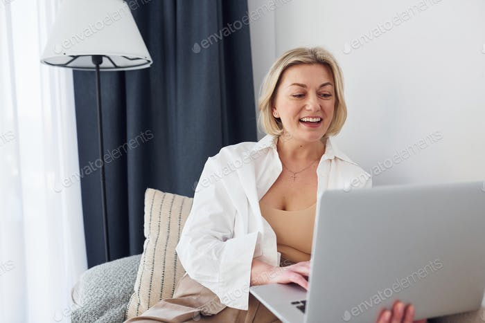 Middle-aged woman in elegant clothes is at home with laptop