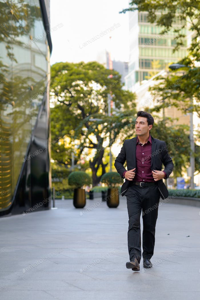 Young handsome Hispanic businessman walking outside the office building