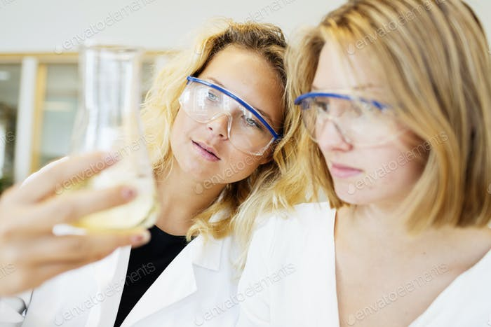 Female students performing experiment in science classroom