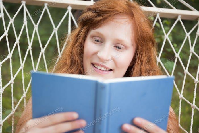 Girl reading a book in the garden