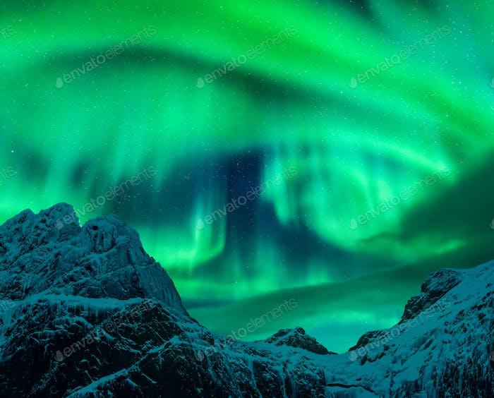 Aurora borealis above the snow covered mountain peak