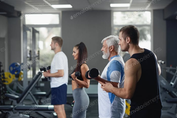 Elderly man doing exercise with group of younger people at gym