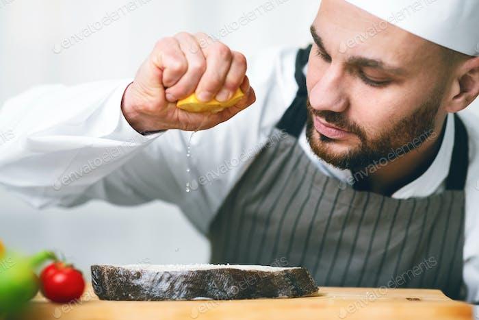 Chef Man Squeezing Lemon On Salmon Steak Standing In Kitchen