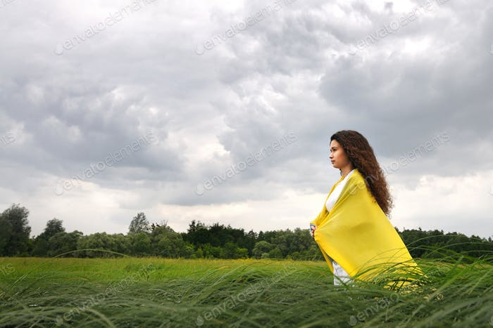 Young woman standing with silk shawl in meadow