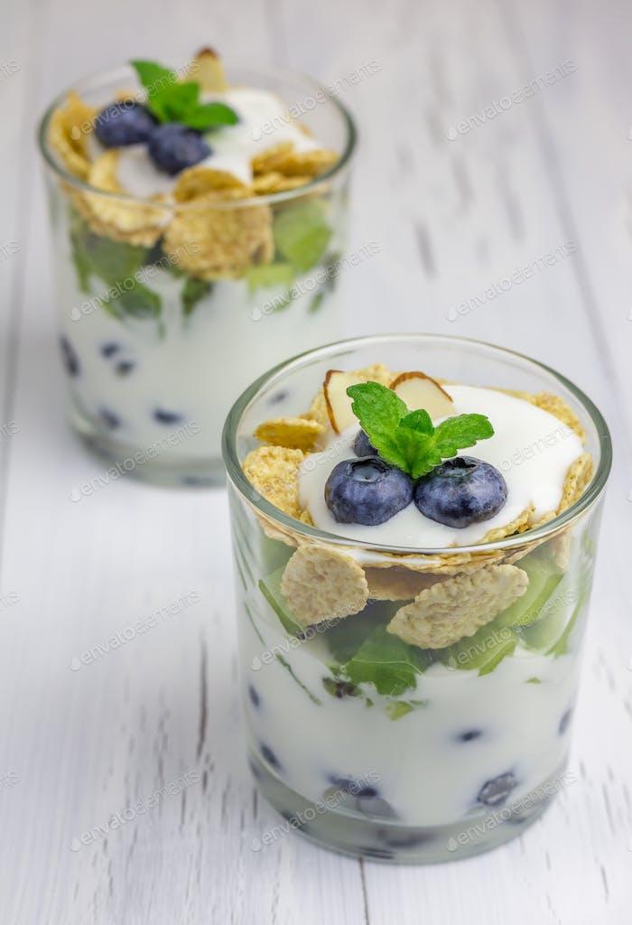Joghurt-Dessert mit Heidelbeere, Kiwi und Getreide im Glas