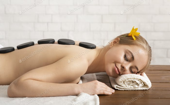 Girl with closed eyes on the table takes spa stone massage