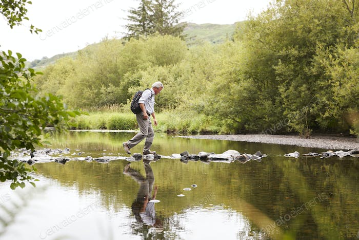 Senior Man Crossing River Whilst Hiking In UK Lake District