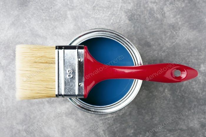 Dose blauer Farbe mit Pinsel auf Steinhintergrund.