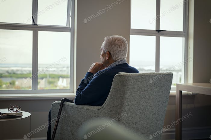 Lonely senior man looking outside the window