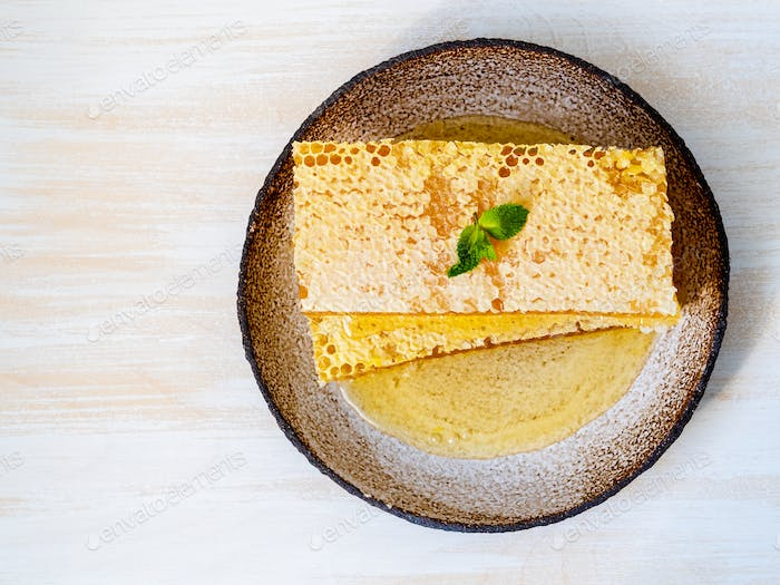 one plate with honey in honeycomb, close-up, on brown ceramic plate, on white wooden table