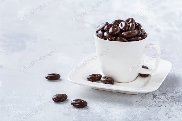 Dark chocolate candies in white coffee cup