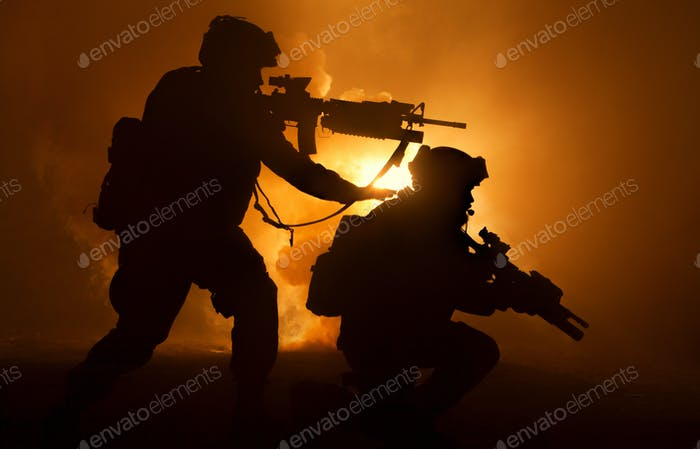 Two attacking soldiers surrounded flame and smoke