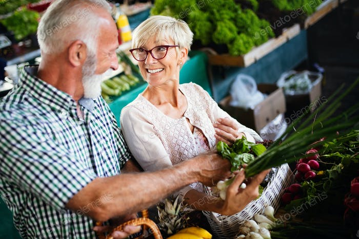 Portrait of beautiful elderly couple in market buing food