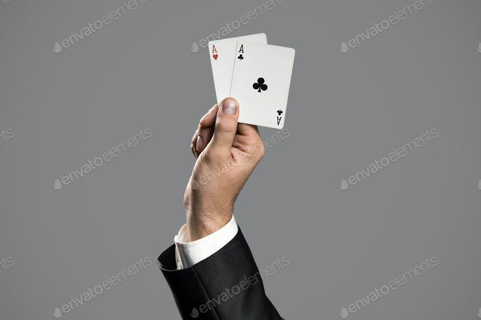 Businessman Holding An Aces On Gray Background. Ace In The Hole.