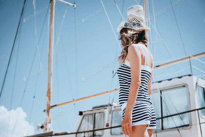 Woman in striped clothes standing near yacht in sunny summer day.
