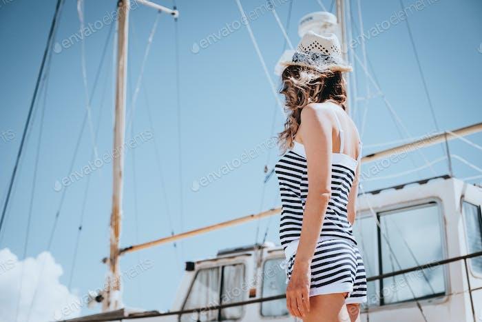 Frau in gestreiften Kleidern stehen in der Nähe der Yacht in sonnigen Sommertag.