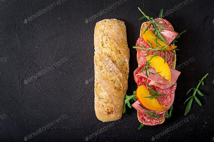 Big sandwich with ham, salami, nectarine and arugula. Flat lay. Top view