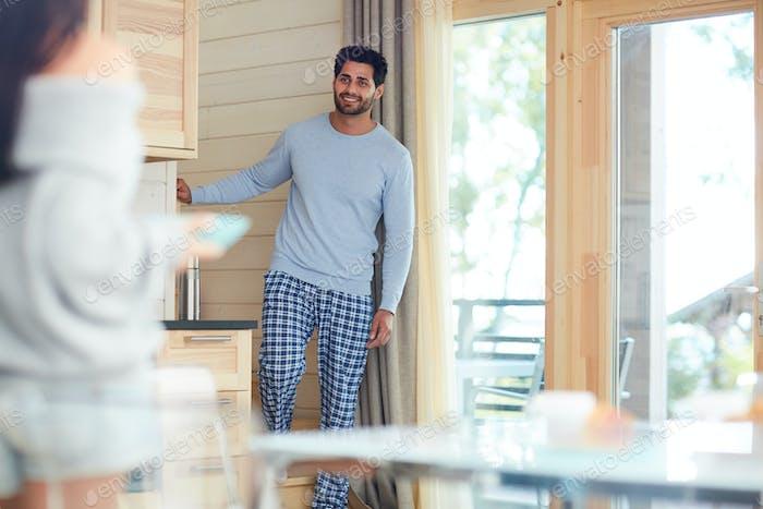 Smiling man in pajamas smiling at wife in kitchen