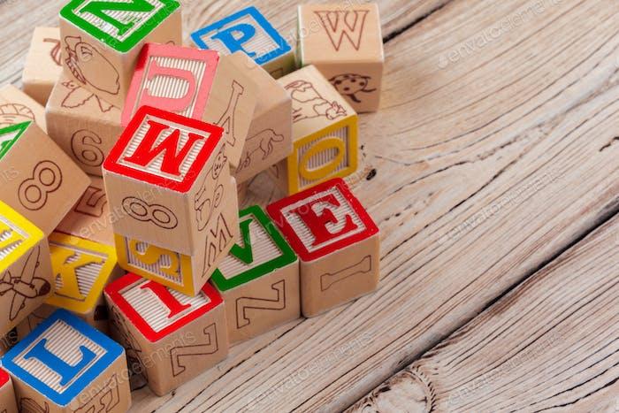 Bloques de juguete de madera multicolores sobre fondo de madera