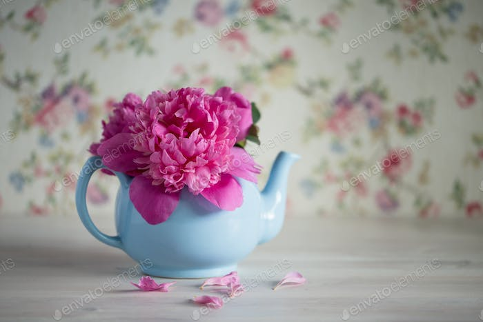 Bouquet of pink peonies in turquoise teapot, copy space