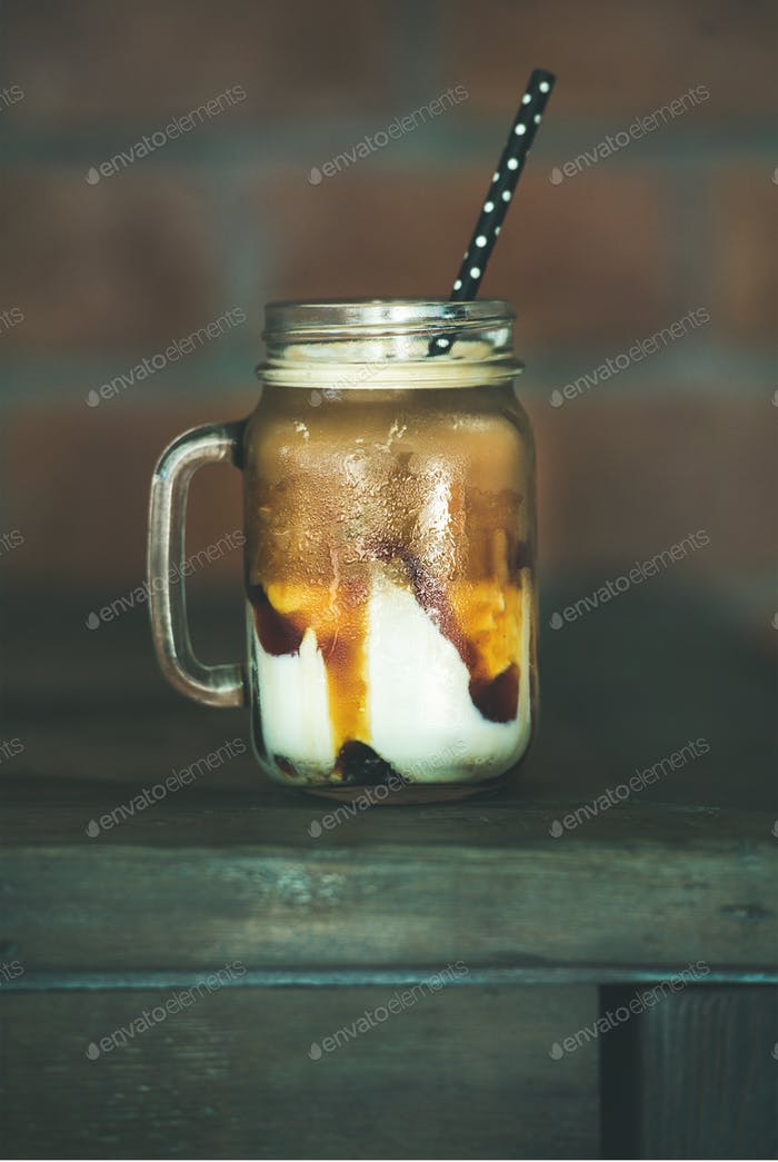 Iced caramel macciato coffee with milk in jar, side view