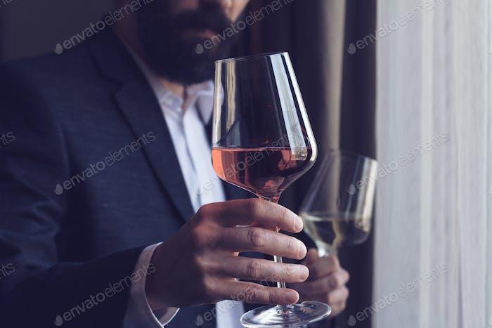 Mann bietet ein Glas Rosenwein