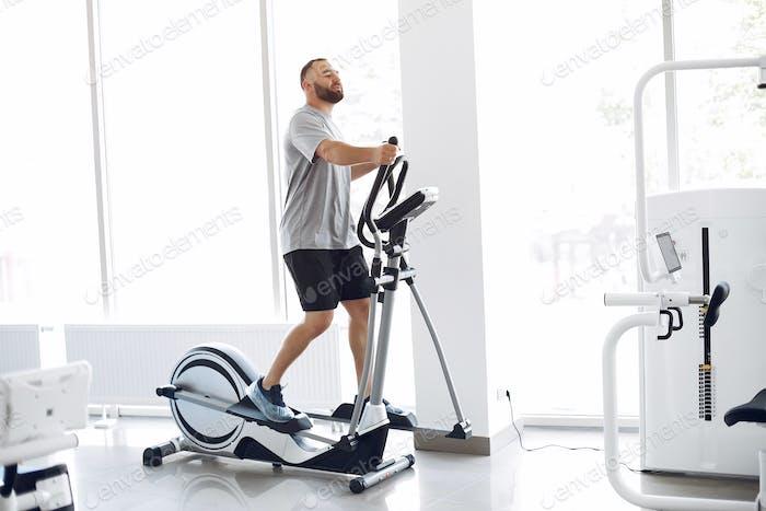 Бородатый человек, использующий спин-велосипед в физиотерапевтической комнате