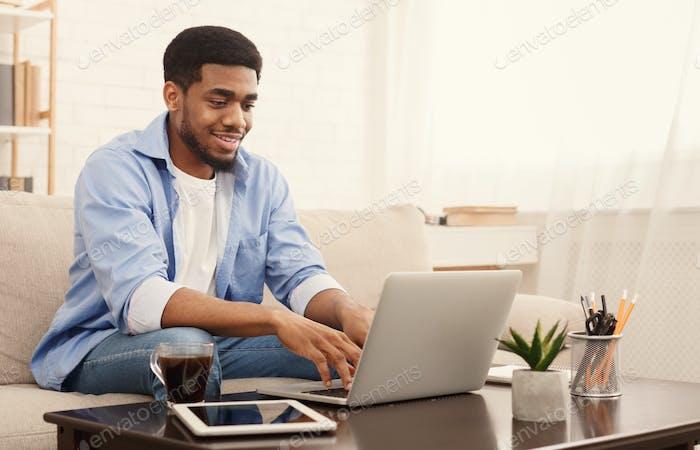 Hombre negro milenario Trabajo en el Ordenador portátil en la oficina en Página de inicio