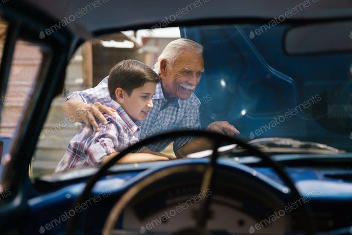 Junge mit Opa suchen Auto Motor von Senior Man