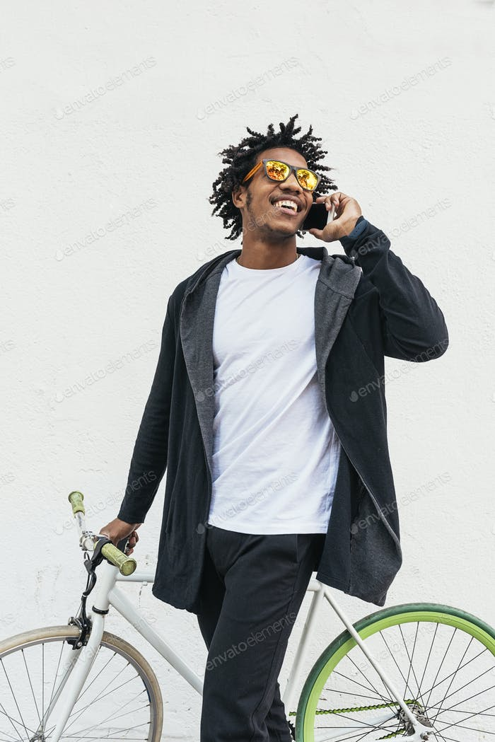 Afro young man using mobile phone and fixed gear bicycle.