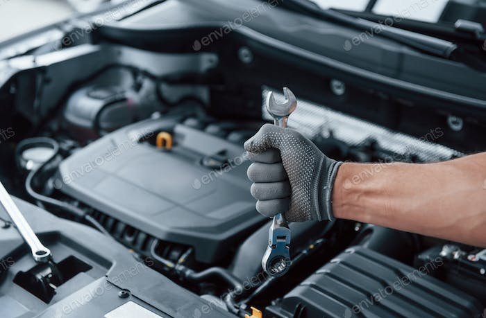 Everything will be fixed. Man's hand in glove holds wrench in front of broken automobile