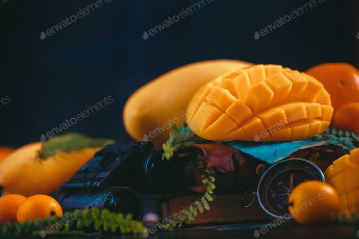 Cut mango halves close-up header with oranges, kumquat, and other tropical fruits. Dark background