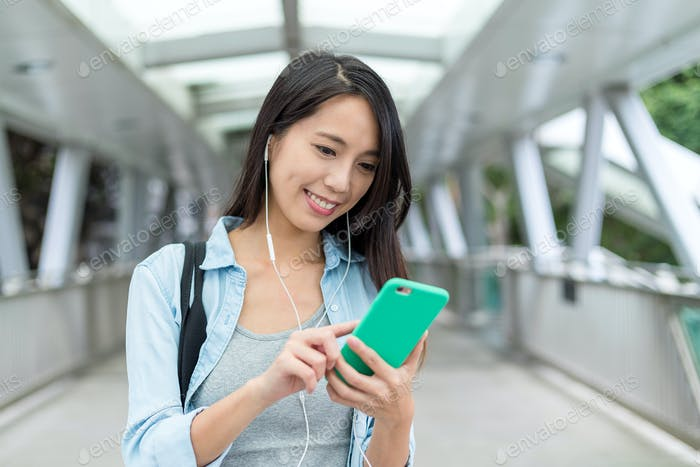 Woman listen to music on mobile phone