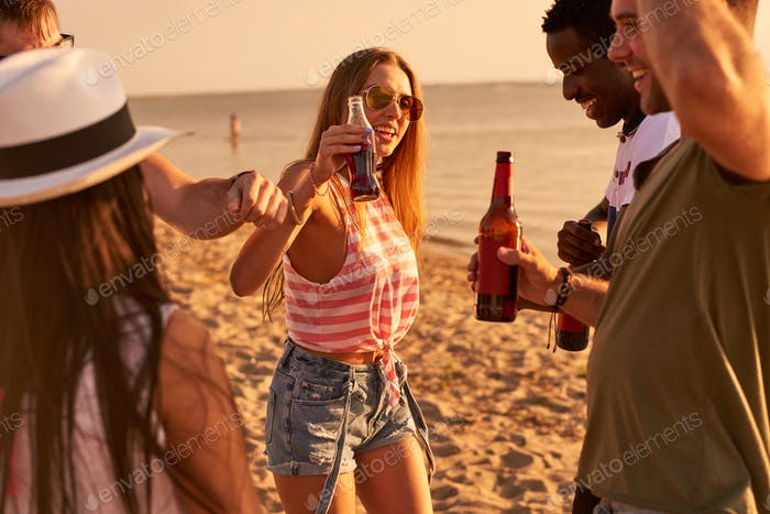 Carefree friends drinking beer at beach party