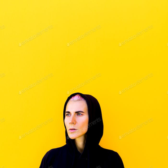 Girl in a hoodie yellow mood urban wall minimal