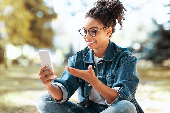 Black Woman Making Video Call On Phone Sitting Outdoors