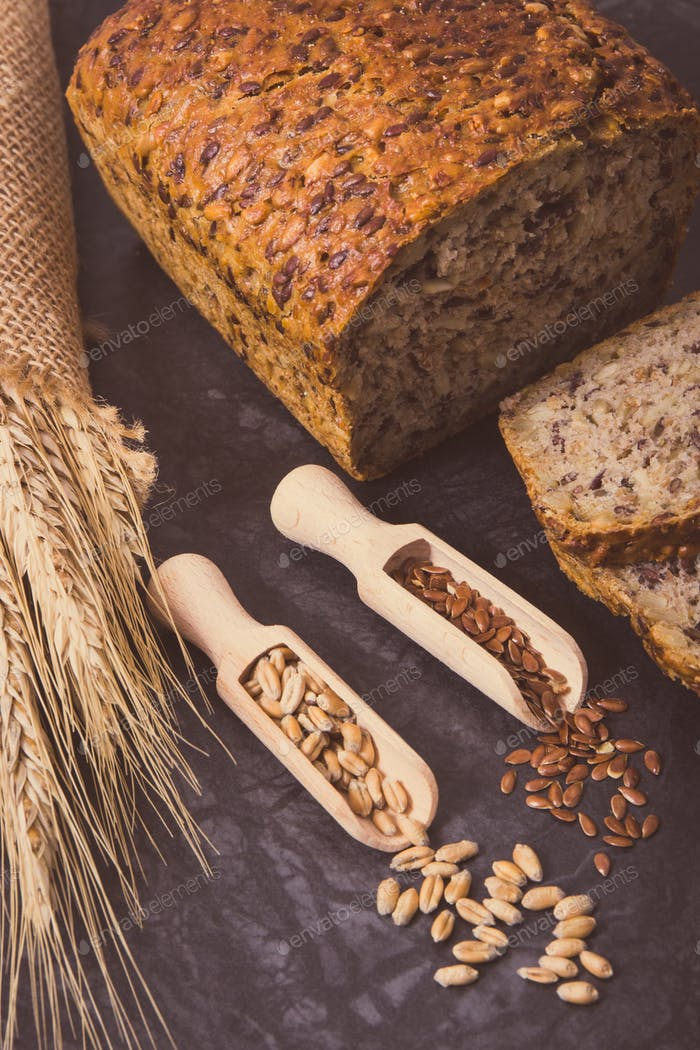 Wholegrain bread for breakfast, ingredients for baking and ears of rye or wheat grain. Vintage photo