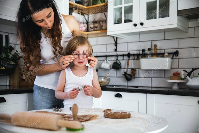 Young mother and her little son baking cookies together at home kitchen