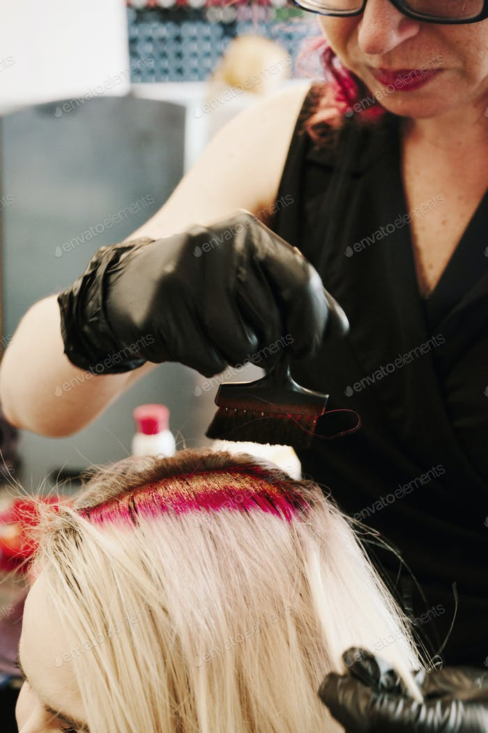 A hair colourist in gloves with client