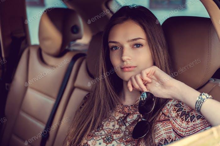 Eine Frau posiert in einem Auto.