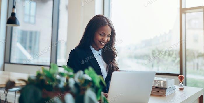 Улыбаясь афро-американский бизнесвумен используя а ноутбук в ее стол