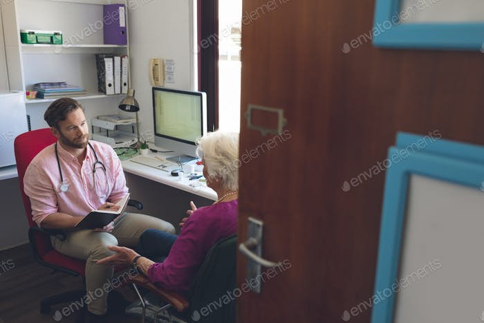 Front view of a Caucasian male doctor and senior woman interacting with each other in clinic room