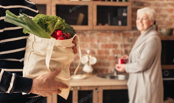 Senior couple unpacking fabric bag with organic food