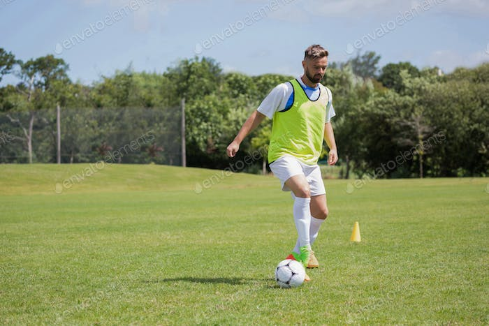 Football player dribbling the soccer on the football ground