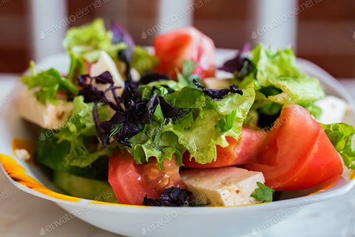 Ensalada griega con verduras frescas en placa cerca