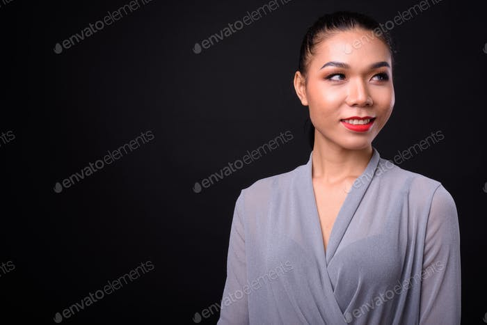 Young beautiful Asian transgender woman against black background