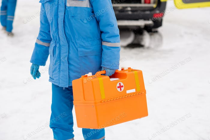 Young paramedic in workwear carrying first aid kit while going to sick person